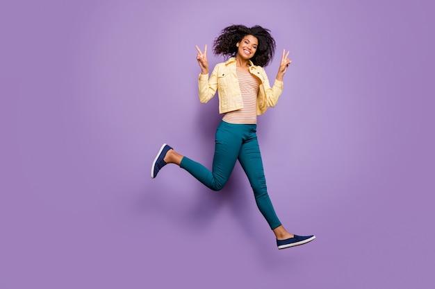 Foto de corpo inteiro virada de menina alegre e radiante em calças, camisa amarela correndo junping mostrando vsign isolado fundo de cor violeta pastel