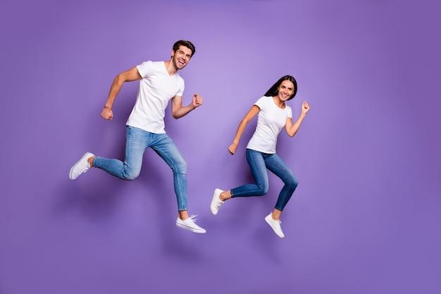 Foto de corpo inteiro virada de um lindo casal de duas pessoas correndo pulando para as vendas em uma camiseta jeans branca calçado jeans isolado fundo de cor pastel violeta