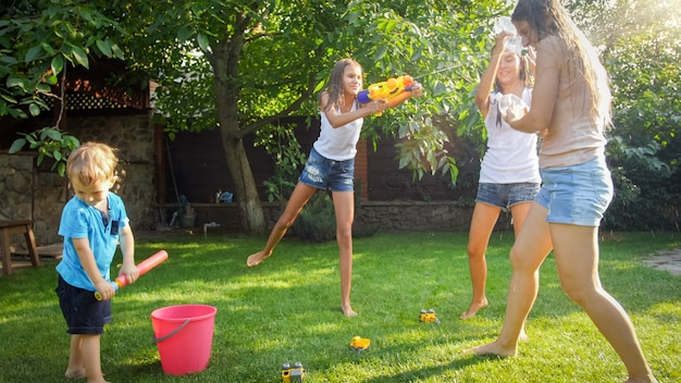 Foto de crianças felizes tendo a luta de arma de água no jardim do quintal da casa. família brincando e se divertindo ao ar livre no verão