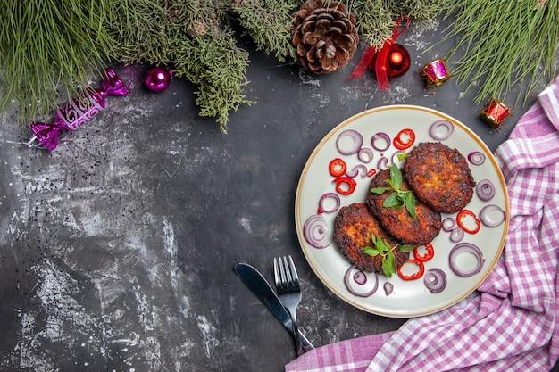 Foto de deliciosas costeletas com anéis de cebola em um prato de carne cinza no chão