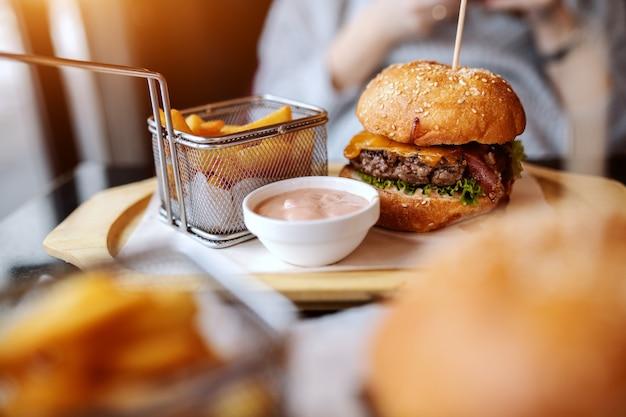 Foto de delicioso hambúrguer, batatas fritas e molho no prato. no fundo, mulher usando telefone inteligente.