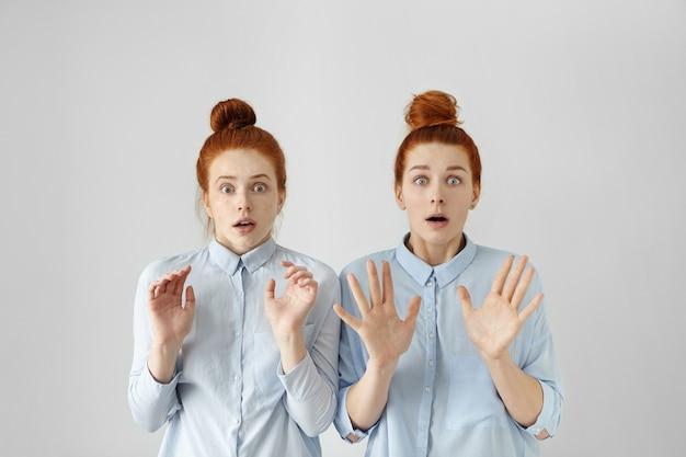 Foto de dentro de casa de duas jovens européias com olhos esbugalhados aterrorizadas e nós de cabelo