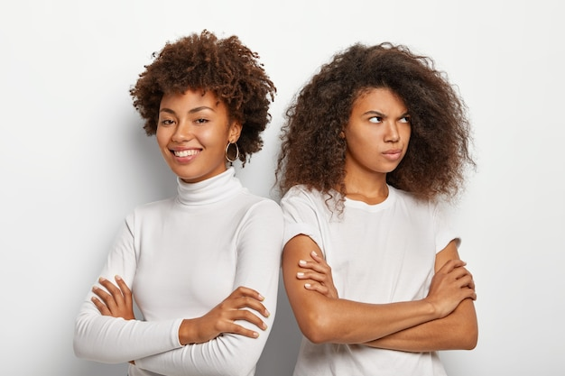 Foto de descontentamento mulher afro se afasta de amiga, mantém o braço dobrado, vestida com roupa casual, pose contra um fundo branco. duas irmãs têm mal-entendido