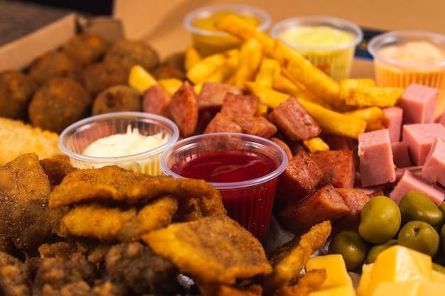 Foto de detalhes de um ketchup e maionese entre uma variedade de lanches