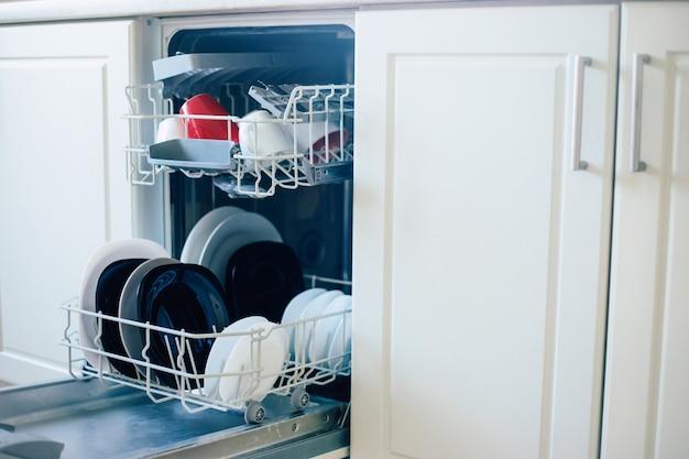 Foto de diferentes talheres na máquina de lavar louça após o trabalho na cozinha doméstica