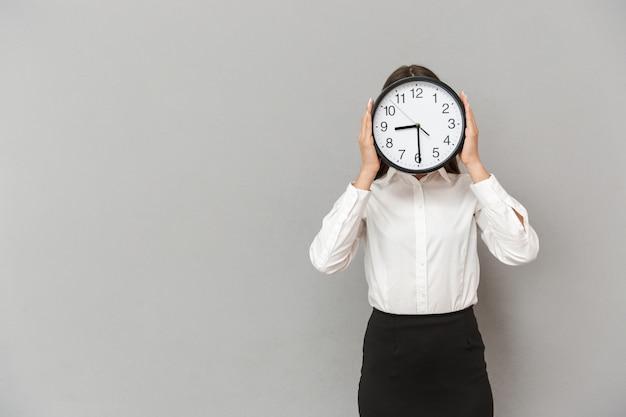 Foto de divertida empresária com roupa formal, cobrindo o rosto com um grande relógio redondo, isolada sobre uma parede cinza