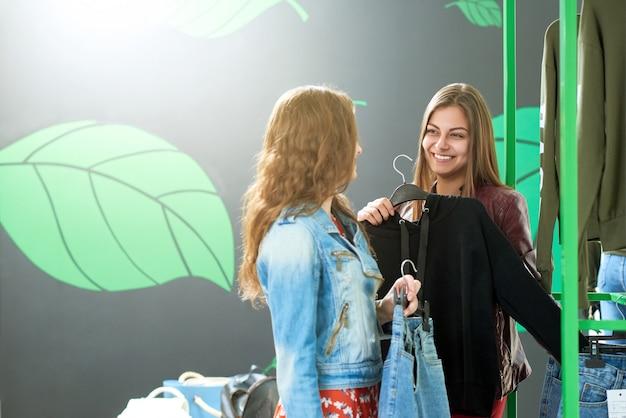 Foto de dois amigos que escolhem calças de brim durante a compra.
