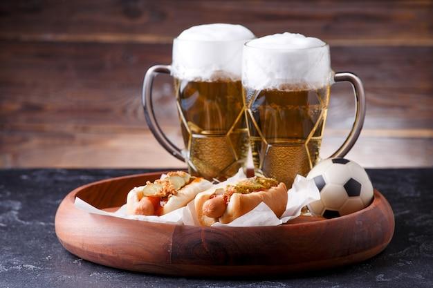 Foto de dois copos de cerveja, cachorro-quente, bola de futebol