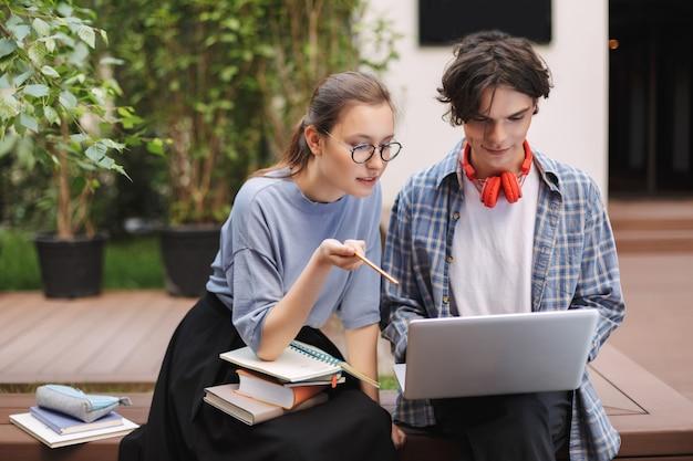 Foto de dois estudantes sentados no banco com livros e trabalhando em um laptop no pátio da universidade