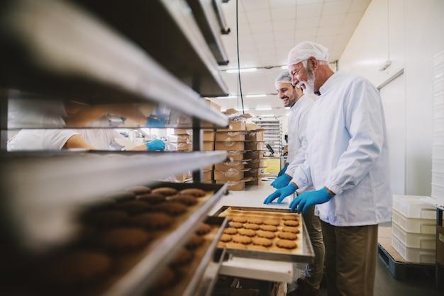 Foto de dois funcionários masculinos de uma fábrica de alimentos em roupas esterilizadas, embalando biscoitos feitos na hora de pé na sala iluminada.