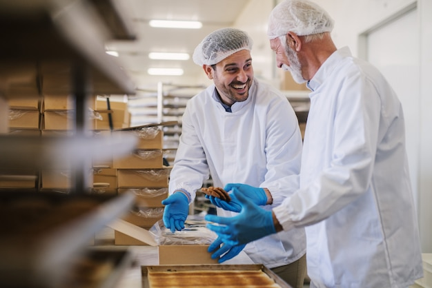 Foto de dois funcionários masculinos de uma fábrica de alimentos em roupas esterilizadas, embalando biscoitos feitos na hora e se divertindo.