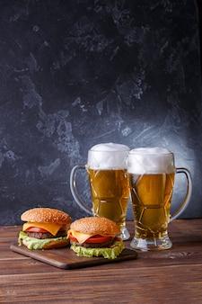 Foto de dois hambúrgueres, copos com cerveja