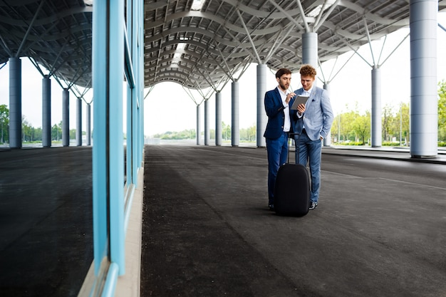 Foto de dois jovens empresários falando no aeroporto e segurando o tablet