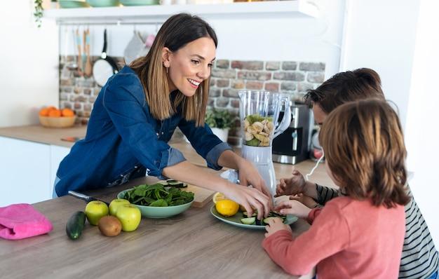 Foto de dois meninos ajudando a mãe a preparar um suco desintoxicante com liquidificador na cozinha de casa.