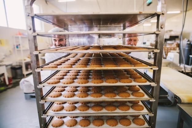 Foto de dois padeiros de uniforme branco empurrando prateleiras cheias de biscoitos recém-assados.