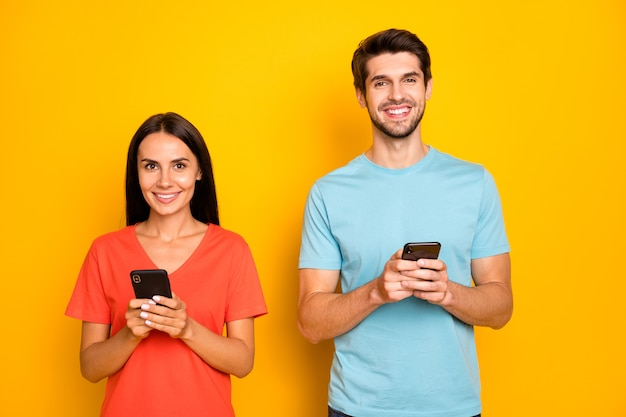 Foto de dois rapazes engraçados, senhora, casal, segurar telefones, braços, ler redes sociais, postar comentários, vestir camisetas casuais azuis laranja parede amarela isolada