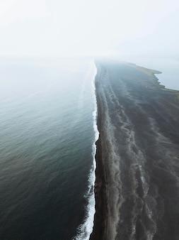 Foto de drone da praia de areia preta de reynisfjara na islândia