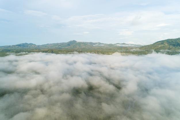 Foto de drone de vista aérea de ondas de nevoeiro fluindo na floresta tropical de montanha. imagem de vista de olho de pássaro sobre