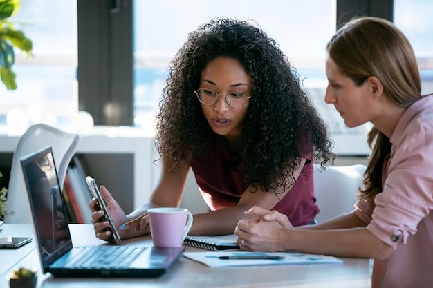Foto de duas belas mulheres de negócios trabalhando em conjunto com o laptop enquanto falava sobre notícias de emprego no escritório.