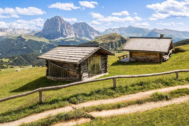 Foto de duas cabines de madeira em um pasto com as montanhas ao fundo