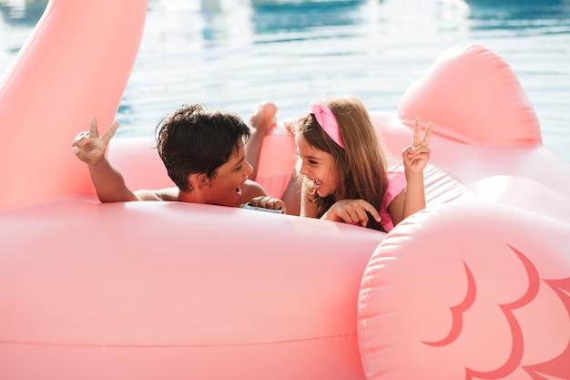 Foto de duas crianças felizes de 6 a 8 anos nadando em uma piscina com anel de borracha rosa, do lado de fora do hotel durante as férias