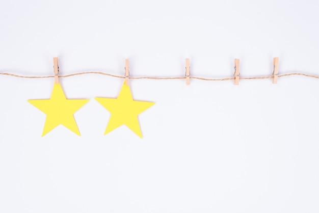 Foto de duas estrelas de avaliação penduradas em um fio preso com pequenos pregadores de roupa em um fundo branco