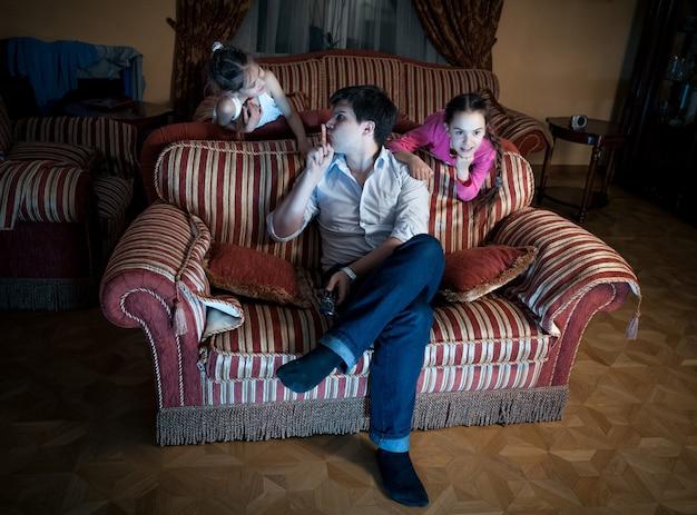 Foto de duas filhas perturbando o pai enquanto assistia tv à noite