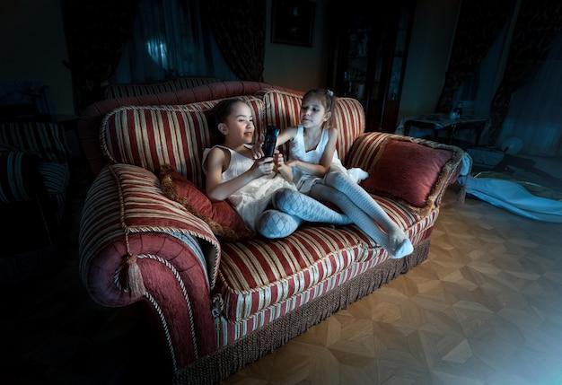 Foto de duas garotas lutando pelo controle remoto da tv no sofá à noite