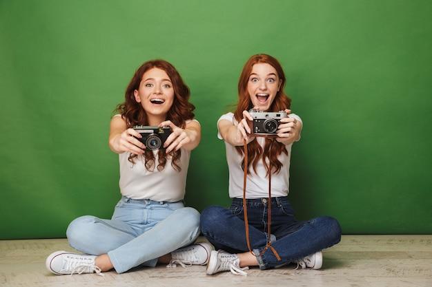 Foto de duas garotas ruivas alegres de 20 anos em jeans, sentadas no chão com as pernas cruzadas e demonstrando câmeras retro, isoladas sobre fundo verde