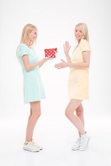 Foto de duas jovens mulheres felizes com um presente sobre uma parede branca