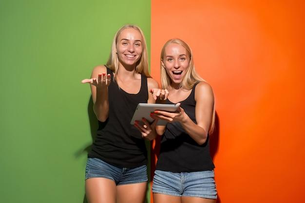 Foto de duas jovens mulheres felizes, olhando para a câmera e segurando laptops no estúdio.