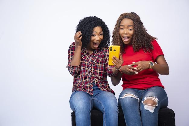 Foto de duas jovens mulheres negras olhando juntas para o telefone, sentindo-se animadas e surpresas