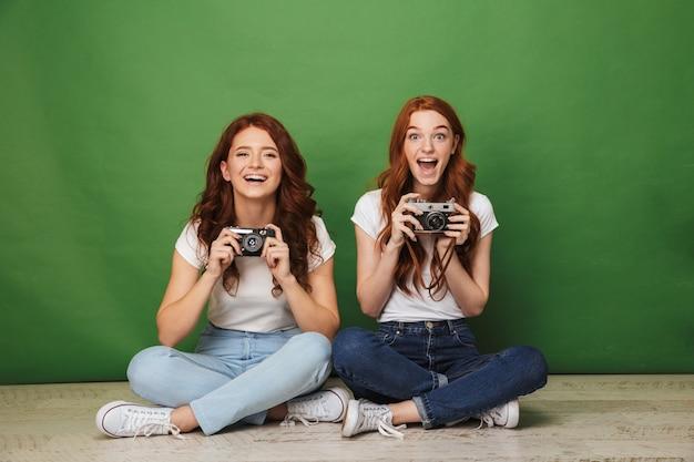 Foto de duas lindas garotas ruivas de 20 anos em jeans sentadas no chão com as pernas cruzadas e segurando câmeras retrô, isoladas sobre fundo verde