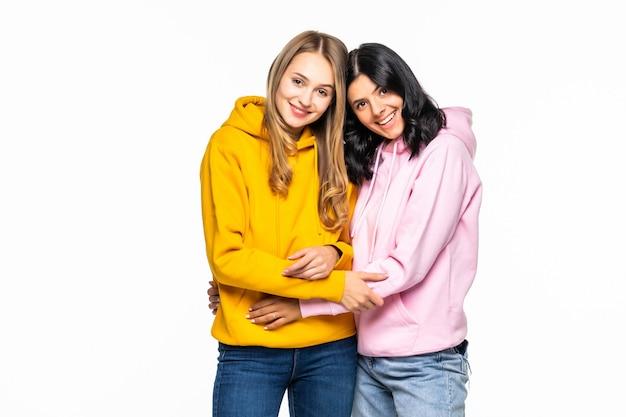 Foto de duas lindas mulheres vestindo moletons casuais e jeans isolado na parede branca