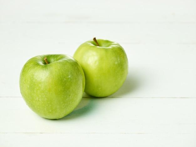Foto de duas maçãs verdes frescas com folhas verdes em uma tabela.