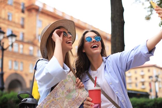 Foto de duas meninas desfrutando de passeios turísticos ao ar livre. lindas mulheres turistas explorando a cidade com mapa e tomando selfie.