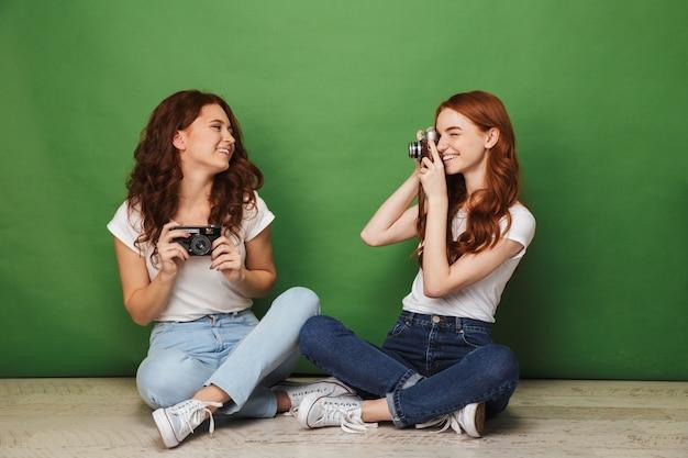 Foto de duas meninas ruivas de 20 anos sentadas no chão com as pernas cruzadas e brincando em paparazzi com fotofonia na câmera retro, isolada sobre fundo verde