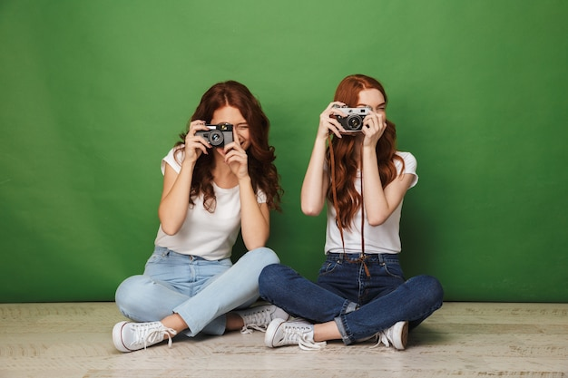 Foto de duas meninas ruivas de 20 anos sentadas no chão com as pernas cruzadas e fotografando você na câmera retro, isolado sobre um fundo verde