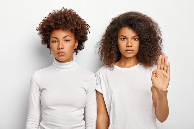 Foto de duas mulheres afro sérias com cabelos crespos e crespos, uma delas fazendo gesto de pare