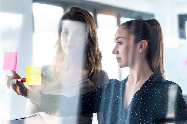 Foto de duas mulheres de negócios trabalhando juntas em vidro de parede com adesivos de post-it no espaço de coworking.