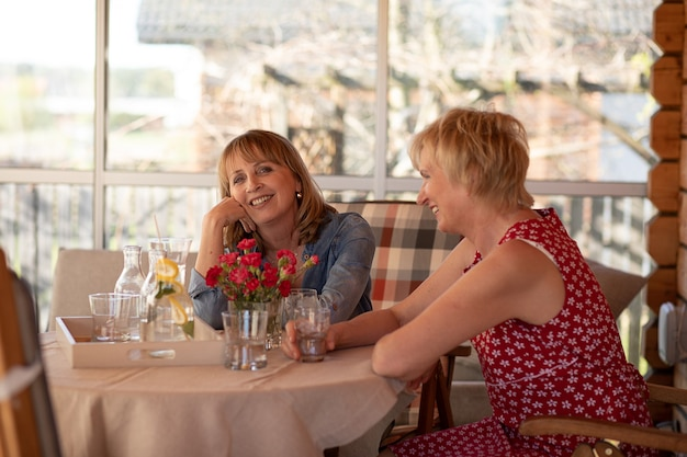 Foto de duas mulheres felizes de 55 anos passando um tempo juntas em casa