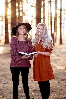 Foto de duas mulheres posando com um livro na floresta, clima de outono