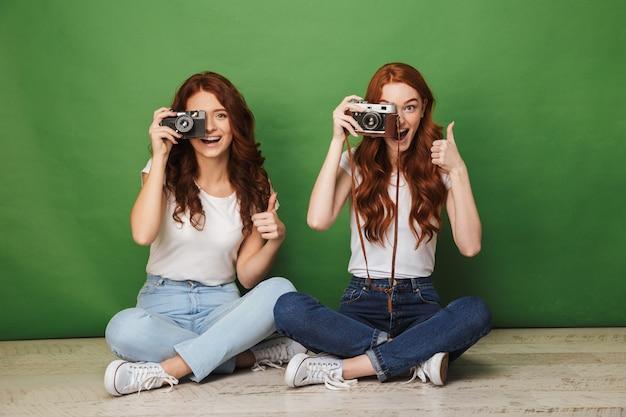 Foto de duas mulheres ruivas de 20 anos sentadas no chão com as pernas cruzadas e fotofografando você na câmera retro, isolada sobre um fundo verde