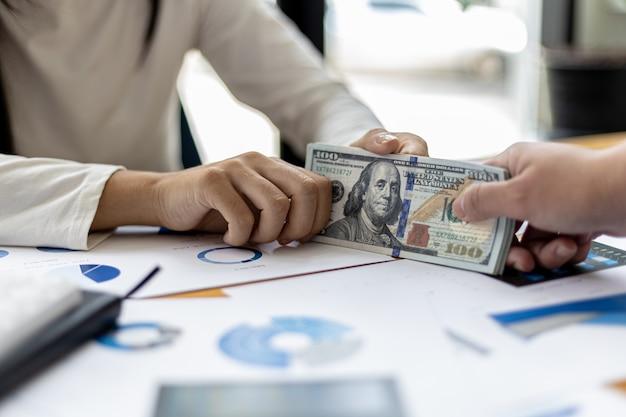 Foto de duas pessoas entregando um dólar, elas são parceiras de negócios que estão cometendo um comportamento corrupto, subornando-as para benefício mútuo ilegal. o conceito de fraude e suborno empresarial.