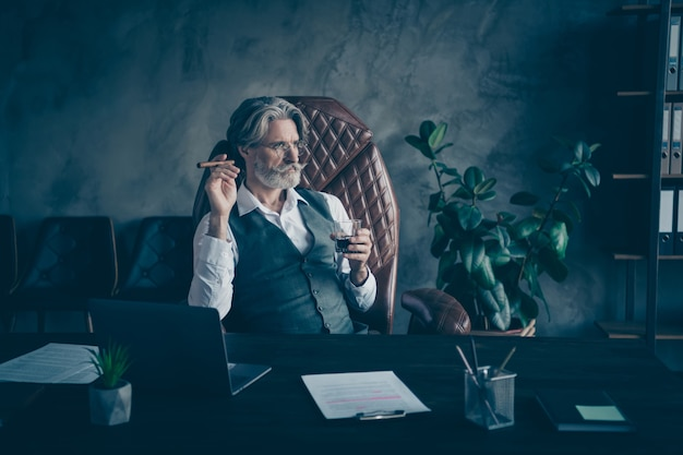 Foto de elegante empresário sério bebendo licor fumando charuto no escritório