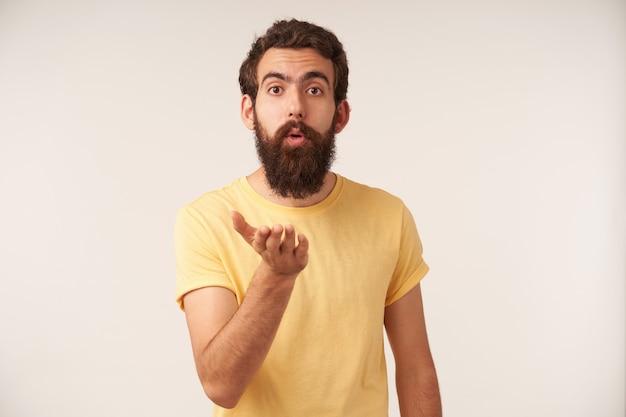 Foto de emoção atraente jovem barbudo flertando, beijo de mosca em pé