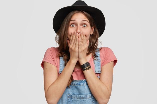 Foto de emotiva jovem jardineira caucasiana cobre a boca com as palmas das mãos, sorri com olhar engraçado e impressionado, vestida com um chapéu preto elegante e macacão jeans, isolada sobre uma parede branca