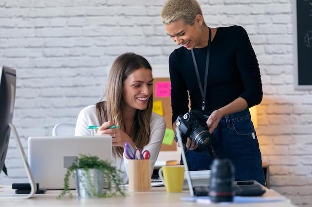 Foto de empresárias sorridentes revendo as últimas fotos na câmera para o próximo trabalho no escritório.