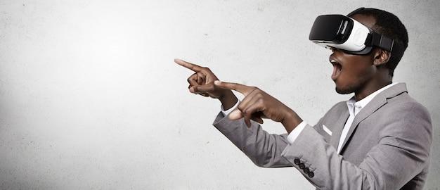 Foto de empresário animado de pele escura experimentando realidade virtual, usando um fone de ouvido 3d, gesticulando como se estivesse assistindo algo surpreendente, abrindo a boca e apontando com os dedos