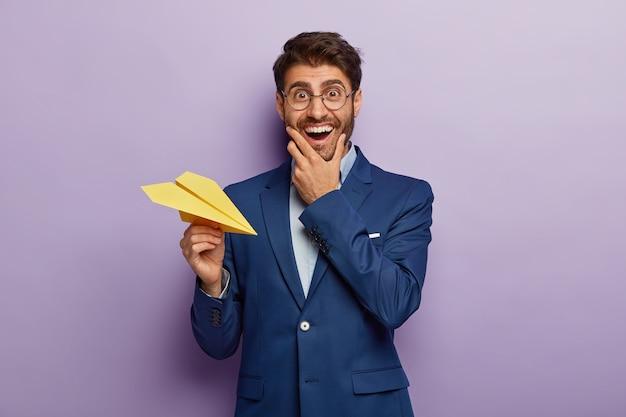Foto de empresário próspero e alegre, dono de uma grande empresa, sorri positivamente, usa terno e óculos transparentes, joga avião de papel